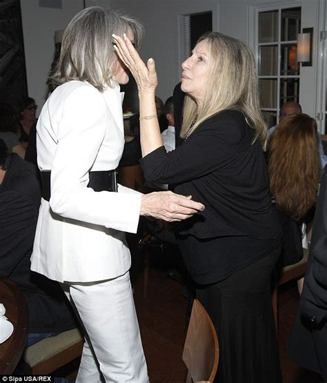Diane Keaton pulls on a woolly hat and scarf as the